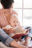 Little bookworm. Young mother holding baby and reading a book royalty free stock photos