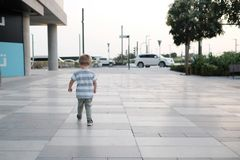 Little booy is walkinbg down the street, view from teh back royalty free stock photo