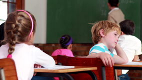 Little bored boy turning to the camera during class. In elementary school stock video footage