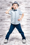 Little boss talks on his mobile phone.Emotional conversation.Kid`s fashion. Royalty Free Stock Photography