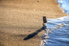 Little bottle happy on sand and sea wave vacation. Nice bottle happy potion vacation creative wave Stock Photography