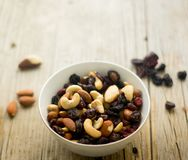 Little bowl with mixed nuts and dried fruits on the wooden table Royalty Free Stock Photo