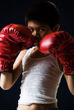 Little boxer. Young asian boy with serious expression wearing red boxing gloves standing on black background Royalty Free Stock Image