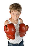 Little boxer. Little boy with boxing gloves is ready to fight and looks very angry Royalty Free Stock Photo