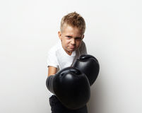 Little boxer fighter standing in boxing gloves and. Little boy standing in boxing gloves on the blank wall background and he ready to fight Stock Photo