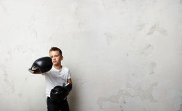 Little boxer fighter standing in boxing gloves and Royalty Free Stock Image