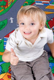 Little boy. Little boy (2,5 years old) sitting on the floor with his thumb up Royalty Free Stock Photos