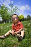 A little boy. Sits in meadow Royalty Free Stock Image