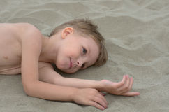 Little boy. Lying on the sand Royalty Free Stock Images