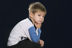 Little boy. Sits and thinks sad Stock Images