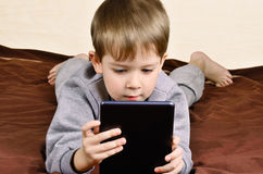 Little boy 5 years lying and playing on a tablet. Horizontal Royalty Free Stock Photos