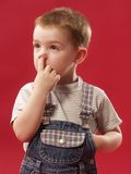 Little boy. Kid of 3-4 years is scratched a finger in a nose Stock Photos