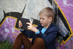 Little boy absorbed into his tablet for educating and playing. Stock Image