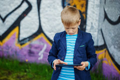 Little boy absorbed into his tablet for educating and playing. Royalty Free Stock Photos