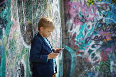 Little boy absorbed into his tablet. Stock Photos