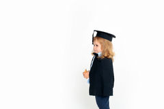 Little boy in academic cap. Little boy kid blond with smiling cute face in black academic squared cap and mantle holding wooden cube in hands standing ob white Royalty Free Stock Photo
