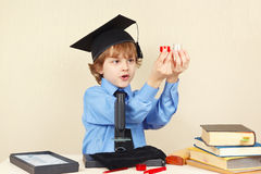 Little boy in academic hat conducts scientific research with microscope Stock Photos