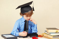 Little boy in academic hat funny thought, seeing something in microscope Stock Photography
