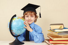 Little boy in academic hat with geographical globe Stock Image