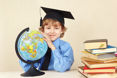 Little boy in academic hat with a globe among old books Royalty Free Stock Photo