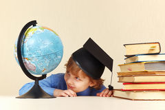 Little boy in academic hat looks at geographical globe Stock Images