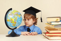 Little boy in academic hat looks at a globe among old books Stock Image