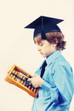 Little boy in academic hat with old abacus on light background, gently toned Royalty Free Stock Image