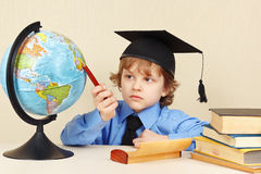 Little boy in academic hat with a pen showing on geographical globe Stock Images