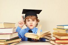 Little boy in academic hat quoted old book Royalty Free Stock Images