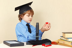 Little boy in academic hat sees the results of research next to microscope Royalty Free Stock Photo