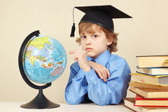 Little boy in academic hat showing on the globe among old books Stock Images