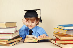 Little boy in academic hat studies old books Stock Image