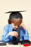 Little boy in academic hat studying something in microscope Stock Images