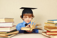 Little boy in academic hat turns the pages of old book Royalty Free Stock Photo