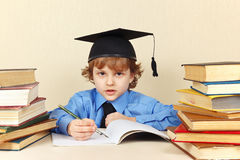 Little boy in academic hat writing pen in notebook among the old books Stock Photos