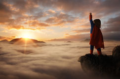 Little boy acting like a superhero. On top of the mountain at sunset with copy space Stock Photo