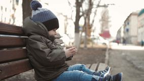 Little boy addictive smartphone sitting on bench in city street. Cute baby boy child with mobile phone on bench outdoor. Little boy addictive smartphone sitting stock video