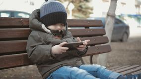 Little boy addictive smartphone sitting on bench in city street. Cute baby boy child with mobile phone on bench outdoor. Little boy addictive smartphone sitting stock footage