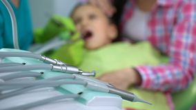 Little boy afraid of dental drill treatment, mother soothing child, background. Stock footage stock video footage