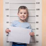 Little boy against police line-up Stock Photography