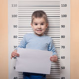 Little boy against police line-up Stock Photos
