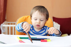 Little boy age of 1 year paints with pens Royalty Free Stock Photo