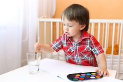 Little boy age of 22 months with paints Royalty Free Stock Photo