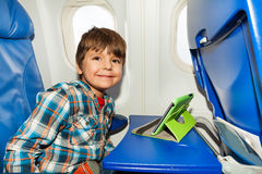 Little boy in airplane chair play tablet pc Stock Photography
