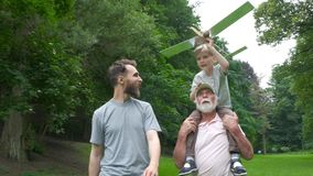 Little boy with airplane model and grandfather raising hands over green park on background enjoying life and nature stock video footage