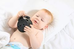 Little boy with an alarm clock Stock Photos