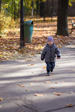 Little boy on alley autumn park. Trash garbage in fundal Royalty Free Stock Photo