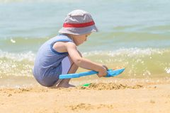 Little boy alone playing on the sea beach with sand royalty free stock images