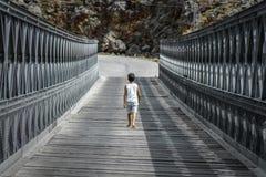 Little boy alone walking on a bridge. Aradena, Crete, Greece Royalty Free Stock Photos