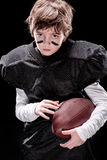 Little boy american football player holding rugby ball and looking at camera Stock Photos